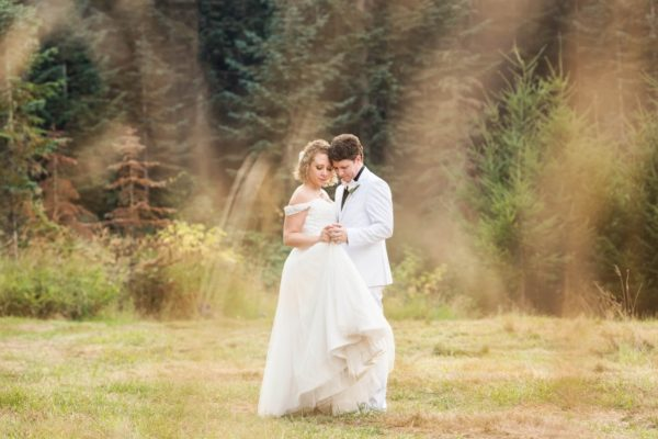 Bride and Groom captured by creative photographer in Pensacola, FL snuggling in the field on their wedding day