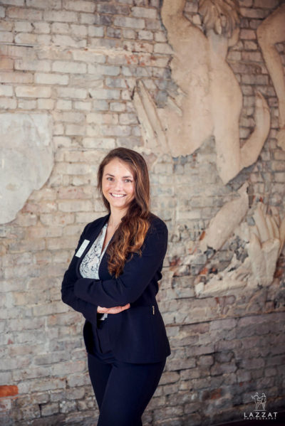 Samm standing in front of brick wall art at 5 eleven palafox