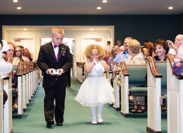 ring bearer and flower girl walking down the aisle