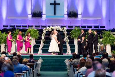 Melinda and Deon kissing at the alter