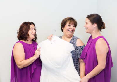Melinda holding her dress with her daughters/Bridesmaids