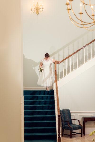Melinda walking down the stairs looking down
