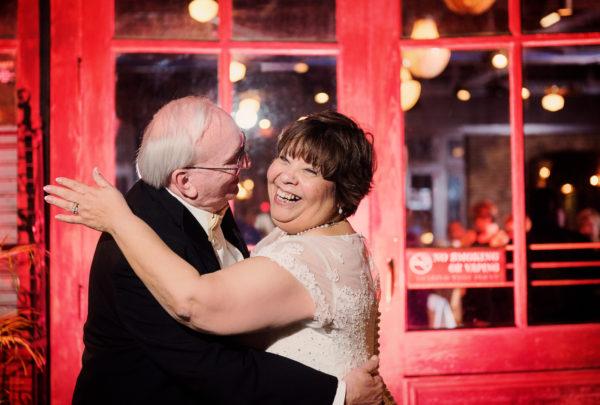 Melinda and Deon hugging outside Seville Quarter - red doors background