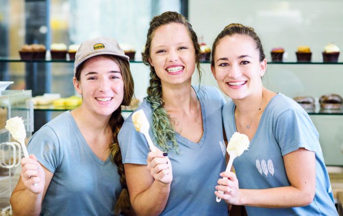 Justine and her team from Blue Jay's Bakery holding frosting covered spatulas