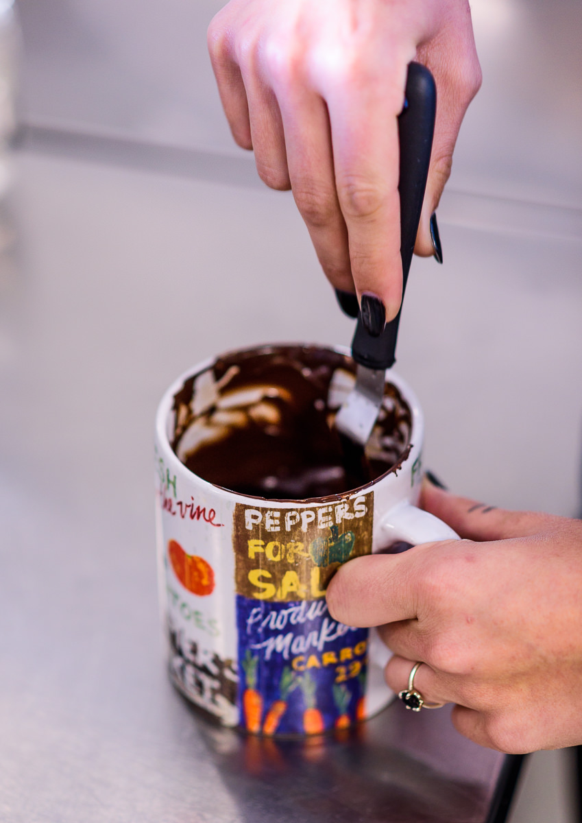 Justine from Blue Jay's Bakery mixing chocolate in a coffee mug
