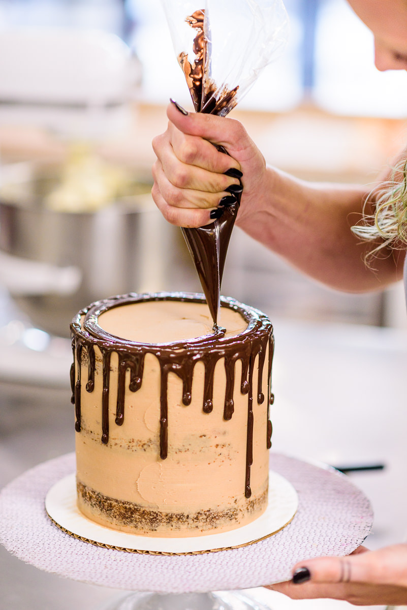 Justine from Blue Jay's Bakery decorating one of her cakes