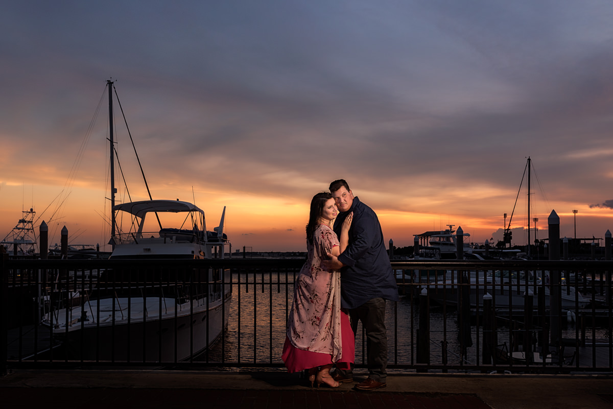 Couple hugging and looking away by the dock at sunset, Sunset Engagement Session in Downtown Pensacola, Lazzat Photography