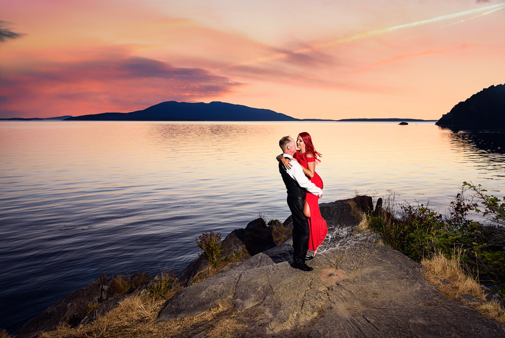 Man picking up woman on the rocks by the water at sunset, red dress, Larrabee State Park Engagement, Lazzat Photography, Engagement photos