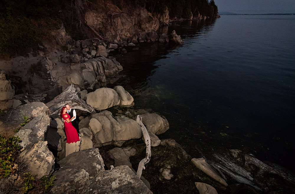 Couple looking out over the water on the rocks, red dress, Larrabee State Park Engagement, Lazzat Photography, Engagement photos