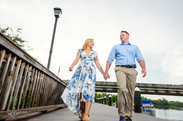Carly and Rick walking and looking at each other | Downtown Milton Riverwalk Engagement