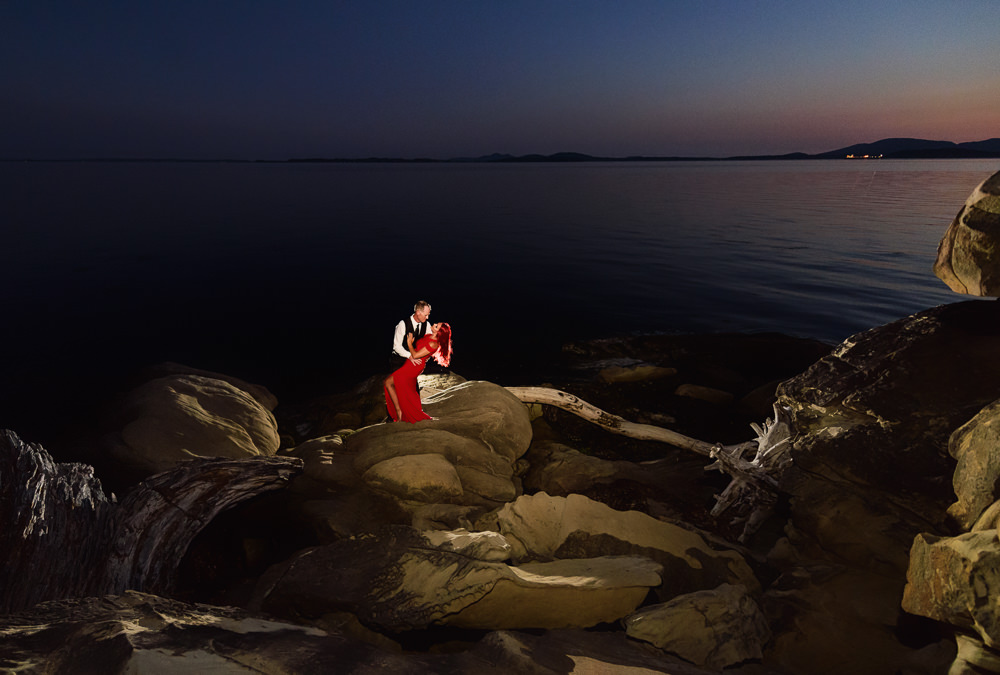 Man dipping woman on the rocks by the water at sunset, red dress, Larrabee State Park Engagement, Lazzat Photography, Engagement photos