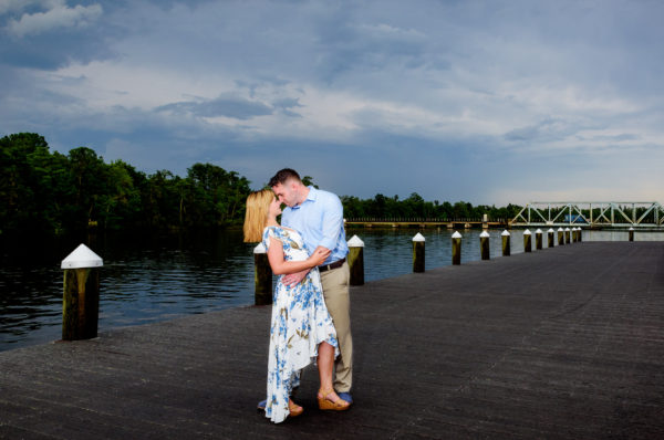 Carly and Rick looking at each other with water in the background | Downtown Milton Riverwalk Engagement