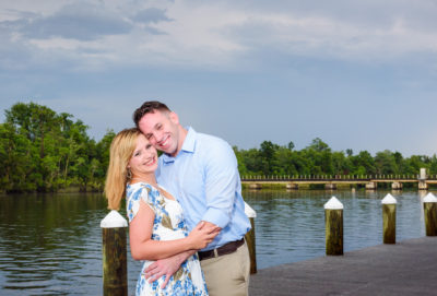 Carly and Rick smiling at camera with water in the background | Downtown Milton Riverwalk Engagement