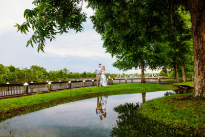 Carly and Rick looking at each other with reflection in water | Downtown Milton Riverwalk Engagement