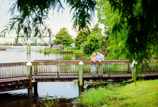 Carly and Rick leaning over a bridge | Downtown Milton Riverwalk Engagement