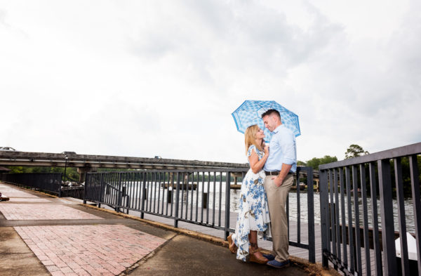 Carly and Rick with an umbrella on the Downtown Milton Riverwalk Engagement