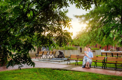 Carly sitting on Rick's lap on a bench | Downtown Milton Riverwalk Engagement