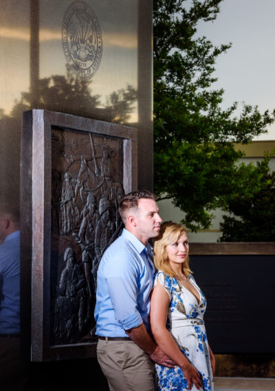Carly and Rick leaning on memorial / Downtown Milton Riverwalk Engagement