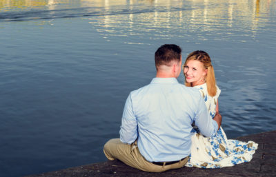Carly and Rick sitting by the water - Carly looking at camera - Downtown Milton Riverwalk Engagement