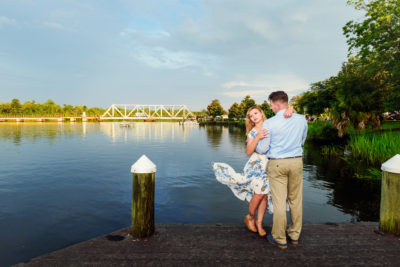 Carly and Rick hugging with water and bridge in the background - Downtown Milton Riverwalk Engagement