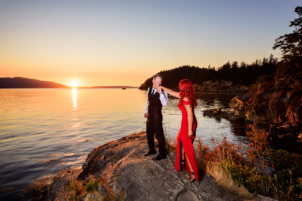 Man kissing his fiance's hand on the rocks by the water at sunset, red dress, Larrabee State Park Engagement, Lazzat Photography, Engagement photos