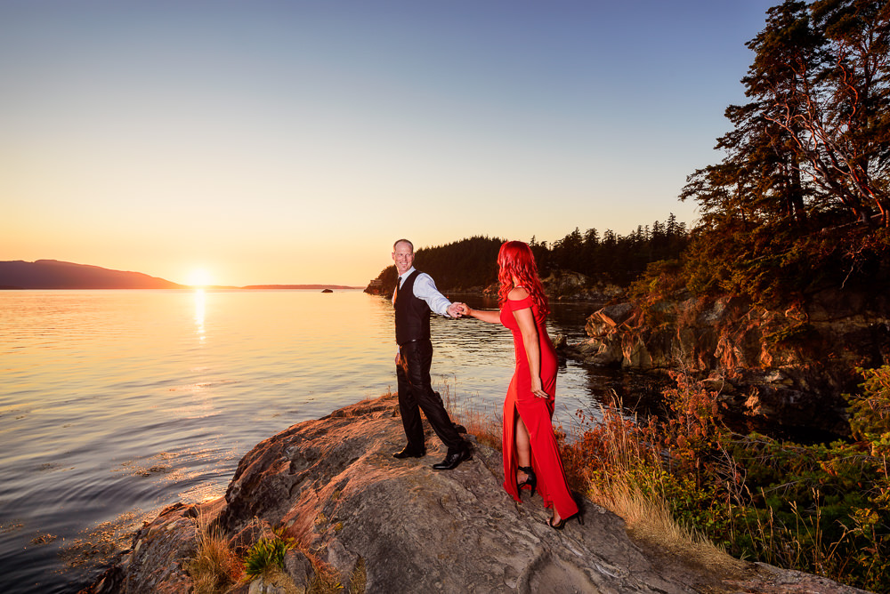 Man leading his fiance on the rocks by the water at sunset, red dress, Larrabee State Park Engagement, Lazzat Photography, Engagement photos