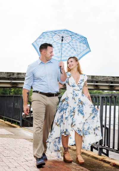 Carly and Rick walking with umbrella | Downtown Milton Riverwalk Engagement