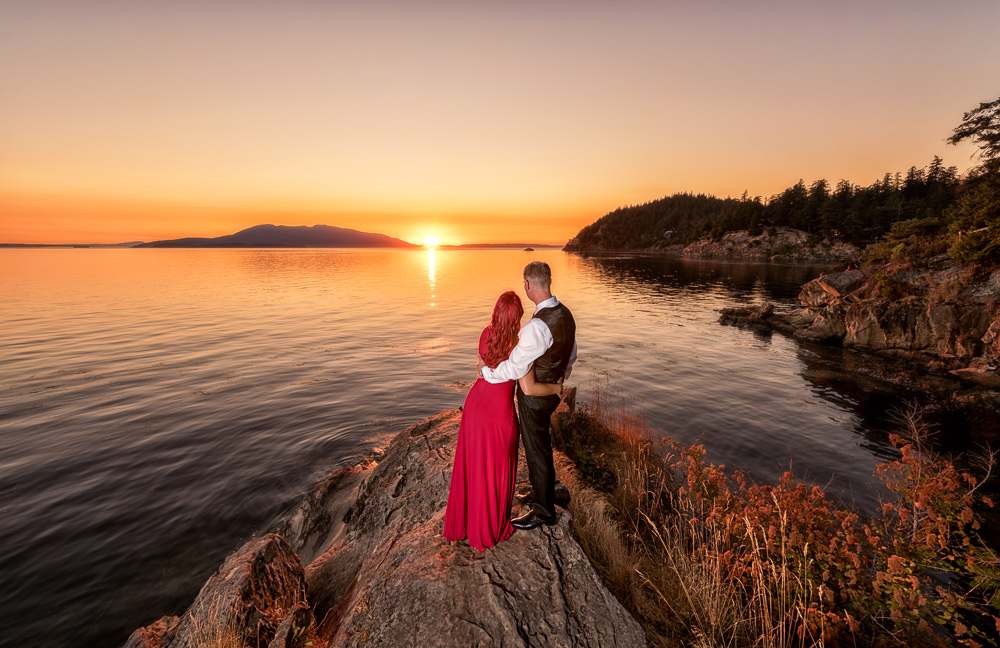 Couple looking out over the water on the rocks at sunset, red dress, Larrabee State Park Engagement, Lazzat Photography, Engagement photos