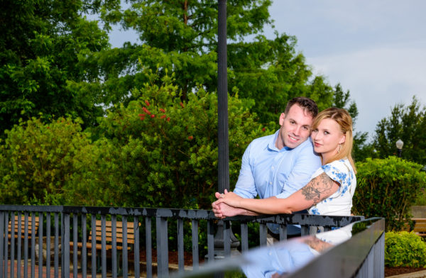 Carly and Rick looking at camera over the railing | Downtown Milton Riverwalk Engagement