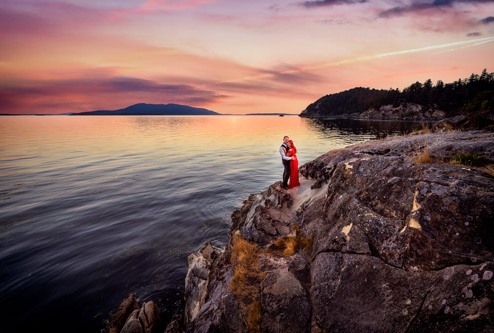 Couple hugging on the rocks by the water at sunset, red dress, Larrabee State Park Engagement, Lazzat Photography, Engagement photos