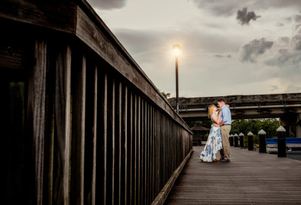 Carly and Rick hugging and looking at each other with a dark sky and street light | Downtown Milton Riverwalk Engagement