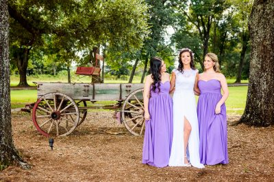 Michelle smiling and her Bridesmaids looking at her in front of the old wagon, Ates Ranch Wedding Barn, Rustic Barn Wedding, purple bridesmaids dresses, Pensacola wedding photographer, Lazzat Photography