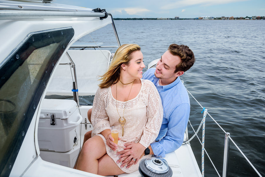Newlyweds smiling at each other on a sailboat, Epic Pensacola Sunset Sailing, Lazzat Photography Sunset Sailing