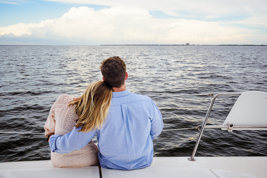 Newlyweds sitting and looking out over the ocean on a sailboat, Epic Pensacola Sunset Sailing, Lazzat Photography
