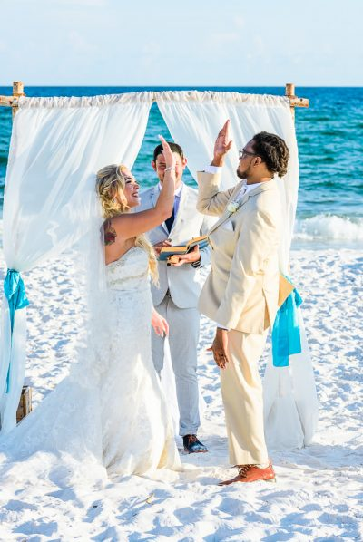 Pensacola Beach Destination Wedding, Desireé and Delaine high fiving during their ceremony, Lazzat Photography