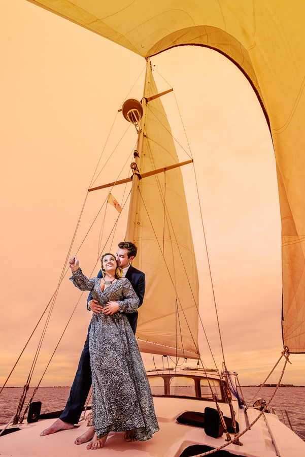 Husband holding his Wife on a sailboat at sunset, Epic Pensacola Sunset Sailing, Lazzat Photography