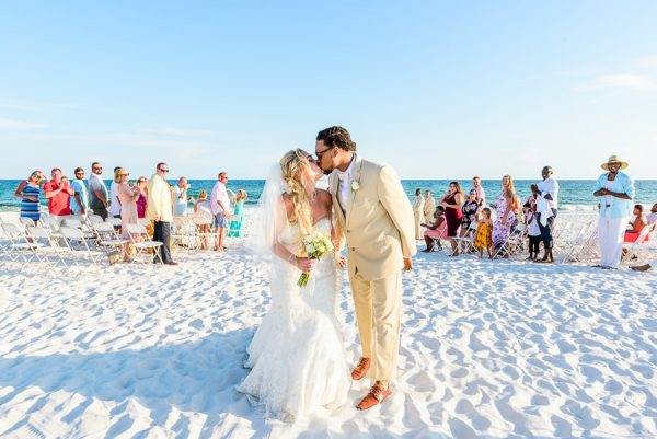 Pensacola Beach Destination Wedding, Desireé and Delaine kissing on the beach with their ceremony in the background, Lazzat Photography