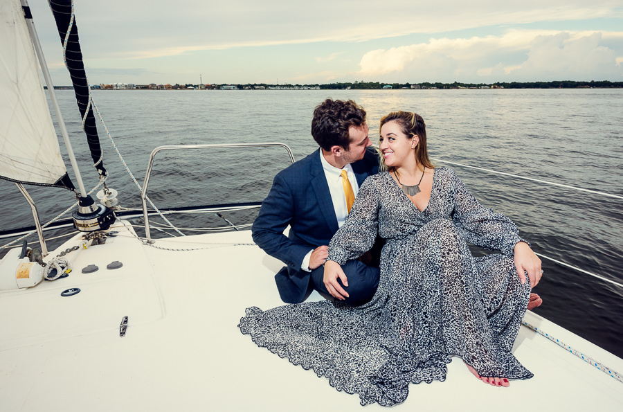 Newlyweds sitting together on a sailboat, Epic Pensacola Sunset Sailing, Lazzat Photography