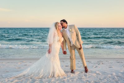 Pensacola Beach Destination Wedding, Delaine kissing Desireé on the cheek in front of the water, Lazzat Photography