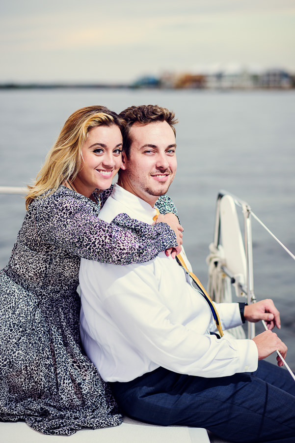 Newlyweds hugging and smiling at the camera on a sailboat, Epic Pensacola Sunset Sailing, Lazzat Photography