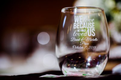 "Close up of Michelle and Brent's wineglasses that say ""we love because he firs loved us Brent & Michelle Price October 7,2018"", Rustic Barn Wedding, Pensacola wedding photographer, Lazzat Photography"