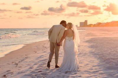 Pensacola Beach Destination Wedding, Delaine and Desireé walking down the beach kissing, Lazzat Photography