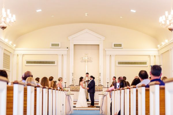 Downtown Pensacola Wedding, Cody and Kerri standing facing each other at the alter of the church, Lazzat Photography