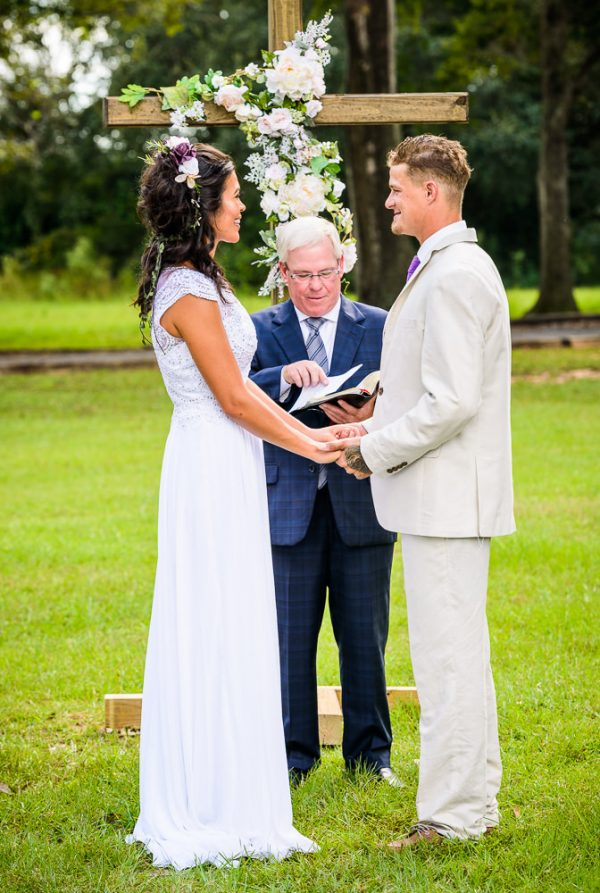 Michelle and Brent holding hands and looking at each other during their wedding ceremony, Ates Ranch Wedding Barn, Rustic Barn Wedding, Pensacola wedding photographer, Lazzat Photography