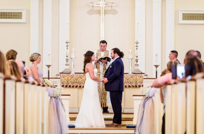 Downtown Pensacola Wedding, close up of Cody and Kerri standing facing each other at the alter of the church, Lazzat Photography