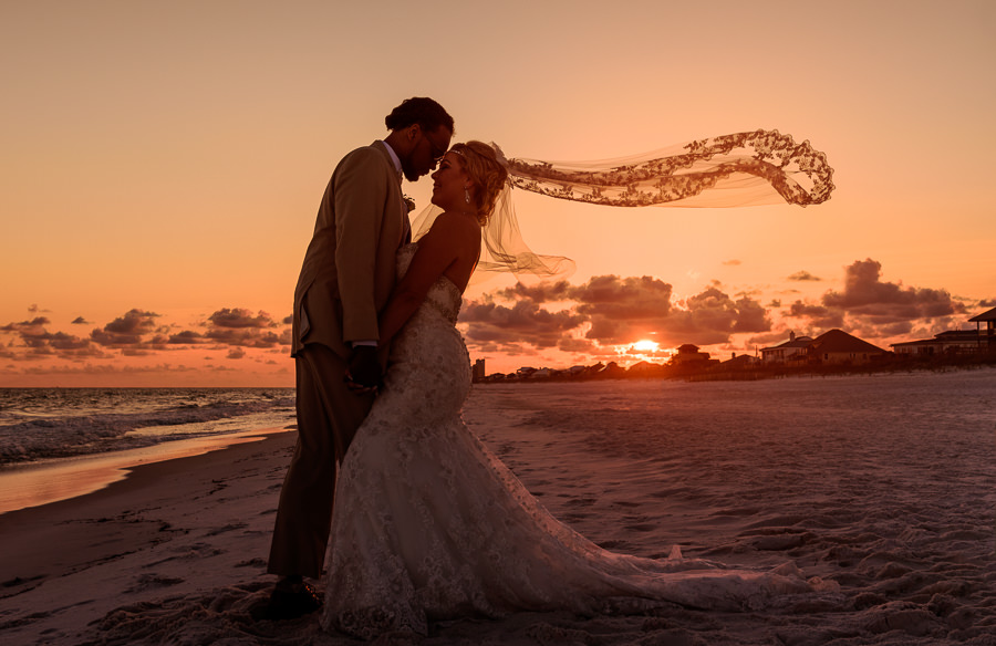 Pensacola Beach Destination Wedding, Delaine and Desireé head to head in the sunset with the veil flying, Lazzat Photography