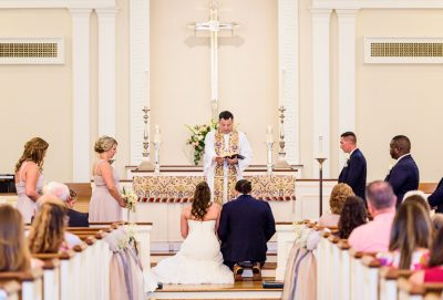 Downtown Pensacola Wedding, Cody and Kerri kneeling at the alter of the church, Lazzat Photography
