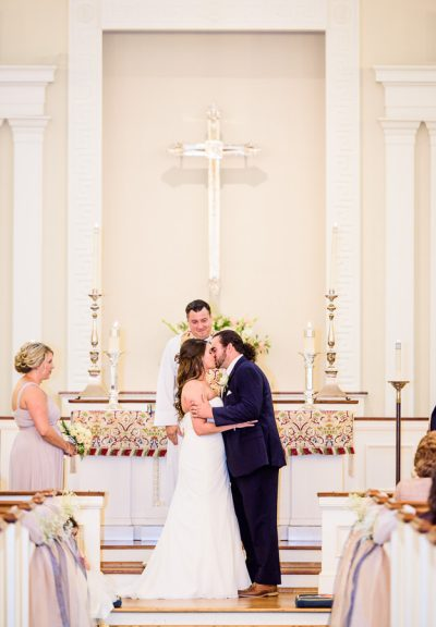 Downtown Pensacola Wedding, Cody and Kerri kissing at the alter of the church, Lazzat Photography