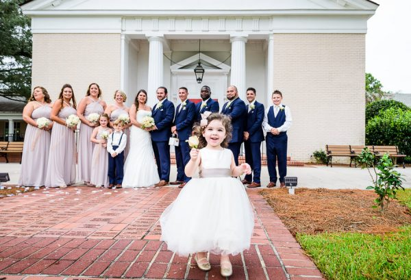 Downtown Pensacola Wedding, Cody, Kerri and their wedding party in the background as girl runs forward, Lazzat Photography