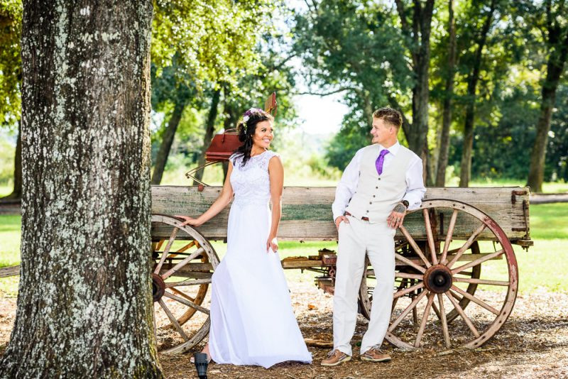 Michelle and Brent standing apart smiling at each other in front of the old wagon, Ates Ranch Wedding Barn, Rustic Barn Wedding, Pensacola wedding photographer, Lazzat Photography